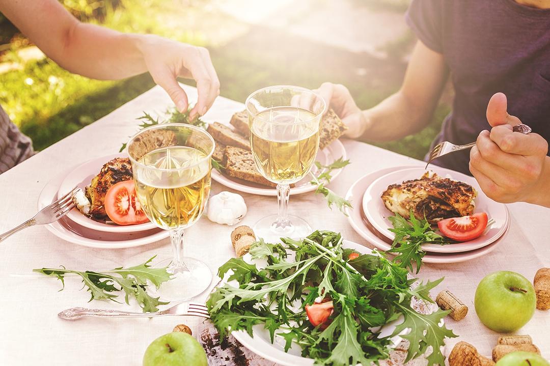 Twee mensen barbecueën en drinken witte wijn.